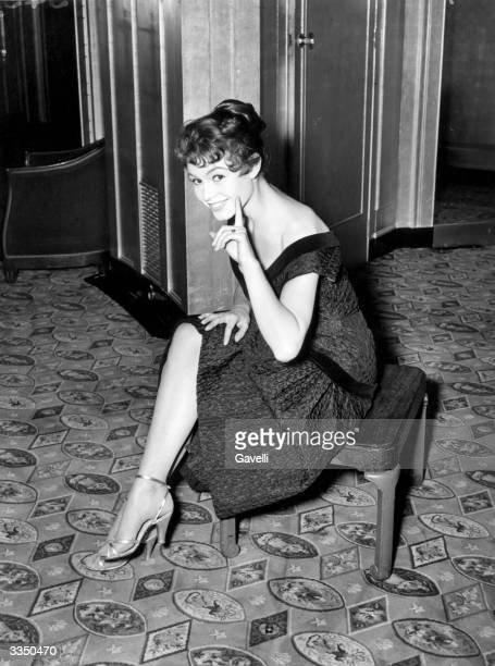 French actress Brigitte Bardot sitting on a stool in a London hotel with her hair dyed a dark shade