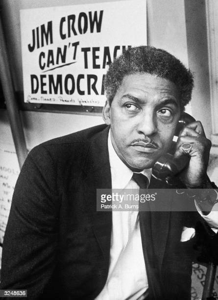 Civil Rights activist Bayard Rustin spokesman for the Citywide Committee for Integration talks on the phone at the organization's headquarters at...