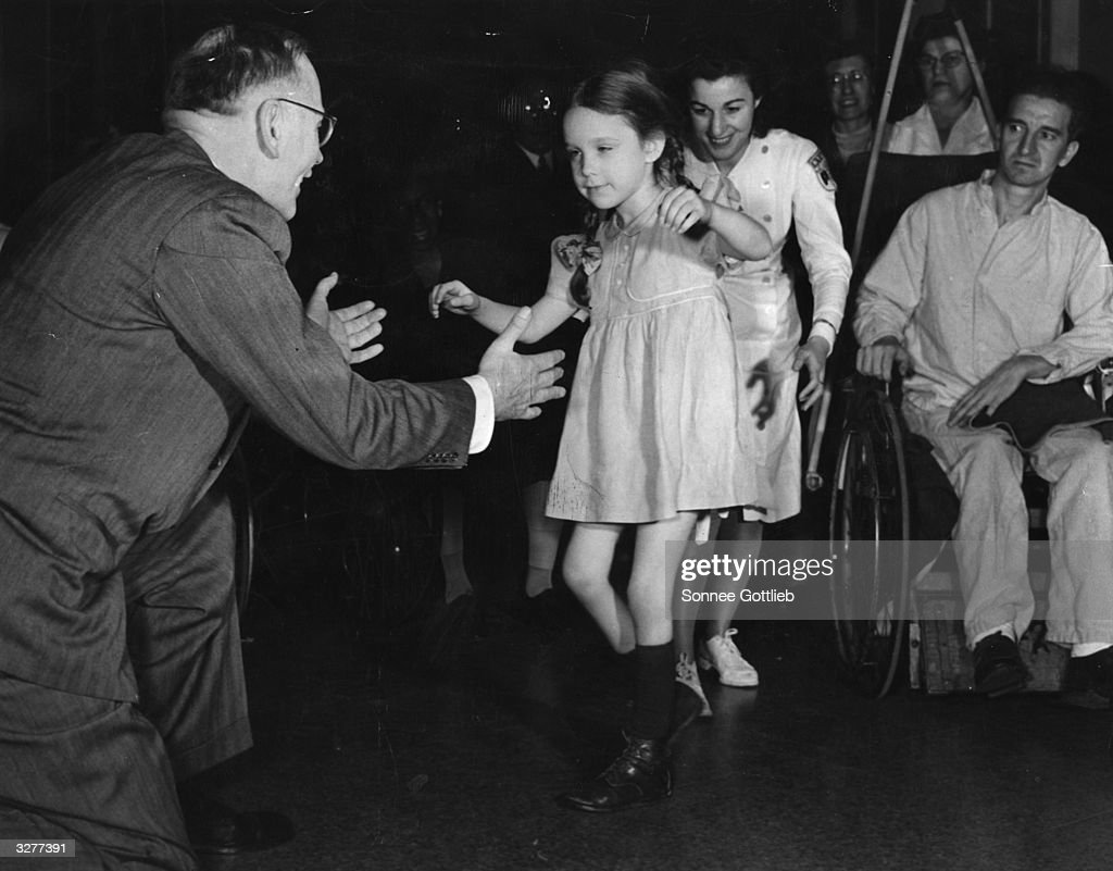 A five year old polio victim walks into the outstretched arms of Doctor George Deaver faculty member of the New York University College of Medicine...