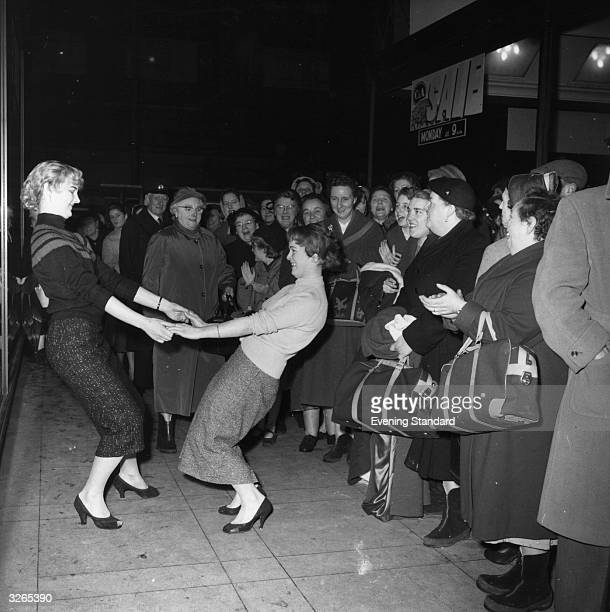 Two young women Kay Paul and Pauline Leach jive for the amusement of the queue outside C A during the January sale