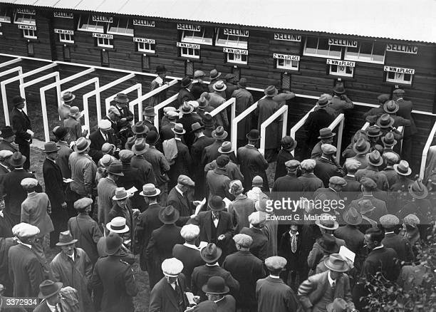 Racegoers placing bets at Britain's first official totalisator or tote system at Newmarket races