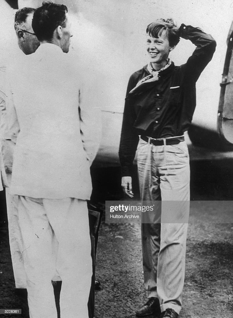 Full-length image of American aviator Amelia Earhart (1898 - 1937) talking to two unidentified men during a break in Calcutta, India, on her flight around the world.