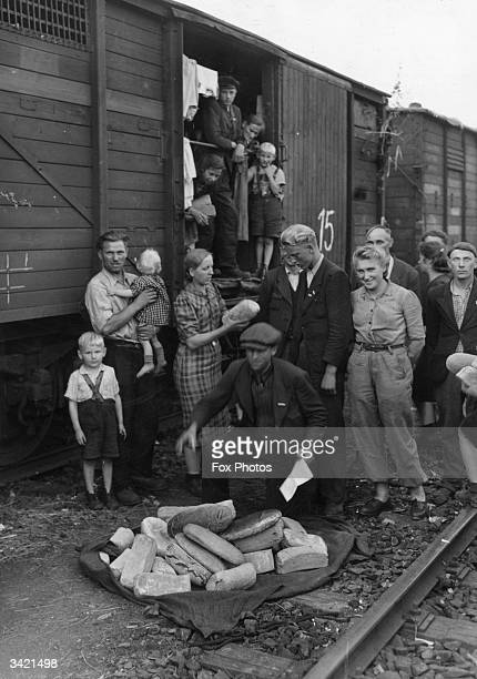 War refugees survivors of a German concentration camp being given bread by UNRRA volunteers at Weimar station Germany before they board a train...