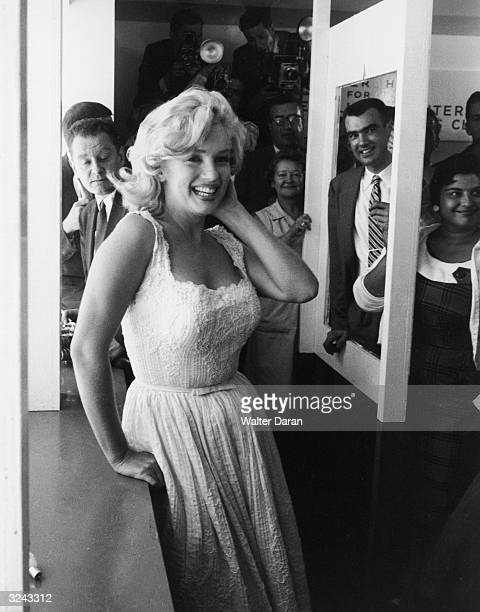 American actor Marilyn Monroe smiles in front of a group of people and photographers at a ribbon cutting ceremony at the TimeLife Building New York...