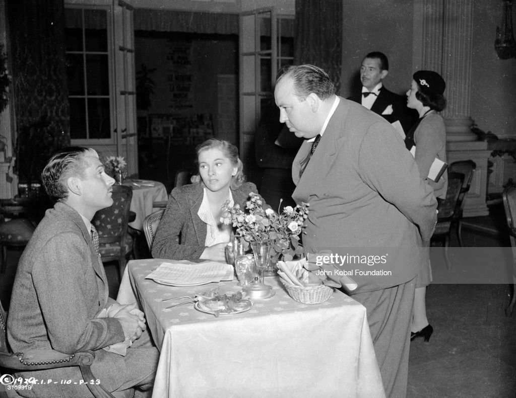 British director Alfred Hitchcock (1899 - 1980) stops to talk to Laurence Olivier (1907 - 1989) and Joan Fontaine, the stars of his latest thriller 'Rebecca'.