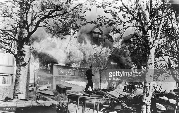 A man runs through wreckage in front of a large house in flames after Luftwaffe air raids secured the Nazi occupation of Norway Narvik Norway World...