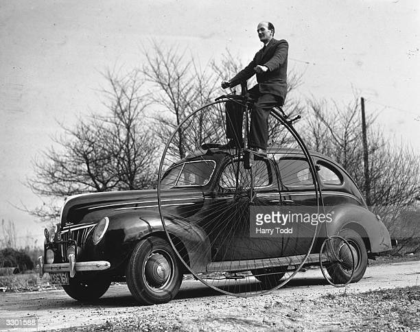 Former racing driver RG J Nash riding his pennyfarthing at home in Weybridge Surrey beside a modern car The pennyfarthing made in 1884 is one of the...