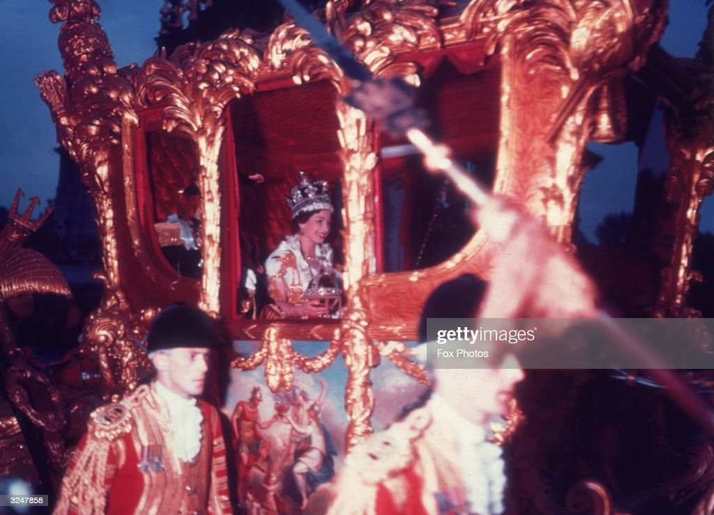 Queen Elizabeth II in the gold coronation coach after her coronation ceremony.