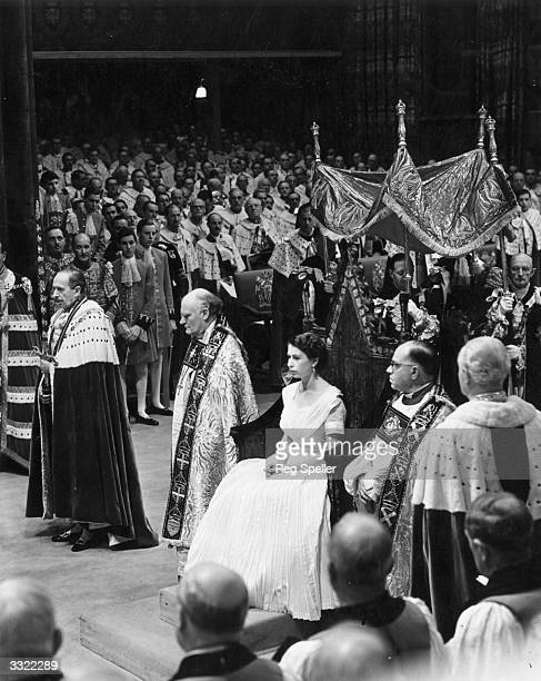 Wearing a simple white dress and surrounded by dignitaries Queen Elizabeth II sits in St Edward's Chair at her coronation ceremony before she is...