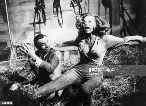 Sean Connery as James Bond up to his tricks with actress Honor Blackman during the filming of 'Goldfinger' at Pinewood studios The film was directed...