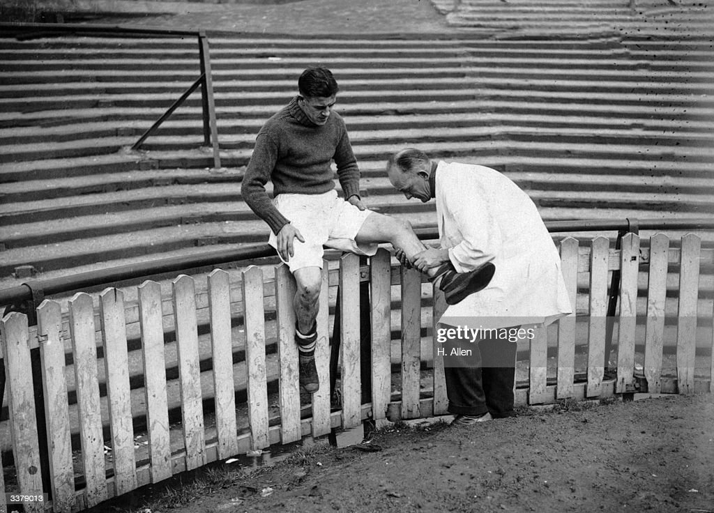 Millwall Football Club centre forward, K Burditt, receives massage during a training session from the club trainer, F Jefferies, at The Den. Millwall are hoping to continue their giant killing FA Cup run in the next round against Manchester City.