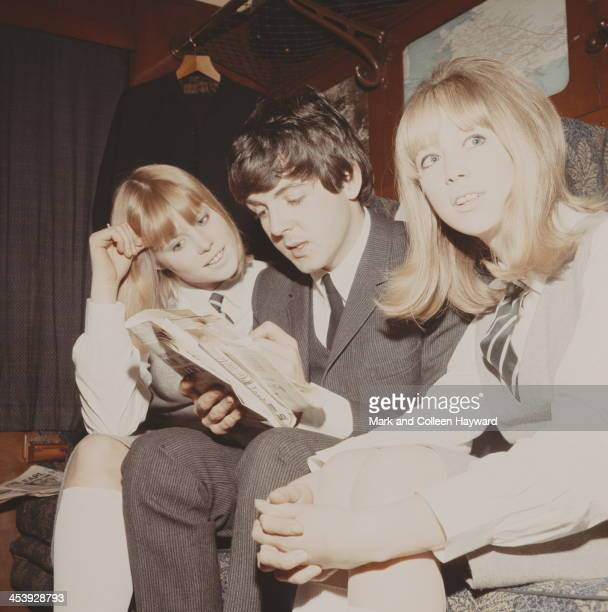 Paul McCartney completes a crossword puzzle with Patti Boyd and another extra on a train from Marylebone Station during the filming of 'A Hard Day's...