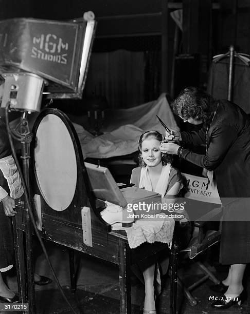 Platinum blonde star Jean Harlow is having her hair trimmed between takes of 'RedHeaded Woman' directed by Jack Conway