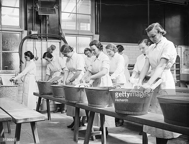 A row of teachers at the Domestic Arts Training College in Cardiff in a laundry class doing the washing in tin baths with scrubbing boards but no...
