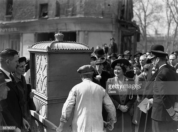 King George VI and Queen Elizabeth inspecting a sedan chair rescued from the ruins of a bombed building in Bath