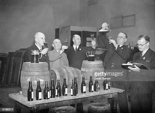 Judges testing and tasting beer at the Brewers' Exhibition held in the Agricultural Hall London F J Bearman has been chairman of the exhibition...