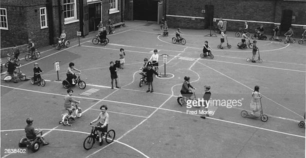 Schoolchildren at the Queen's Park Primary School on Droop Street London learn about Safety First and the Highway Code They are using bicycles and...