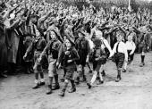 A group of young National Socialists wearing brown caps as in Italy march past a crowd of men saluting at the Third Reich Youth Convention of the...