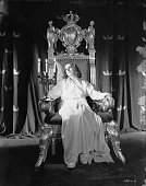 Swedish born American actress Greta Garbo in costume and sitting on a throne for her role in the film 'Queen Christina'