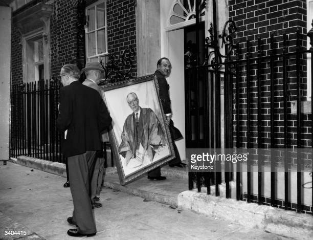 A painting of Prime Minister SIr Harold Macmillan is carried back into 10 Downing Street after the address' 1000 refit