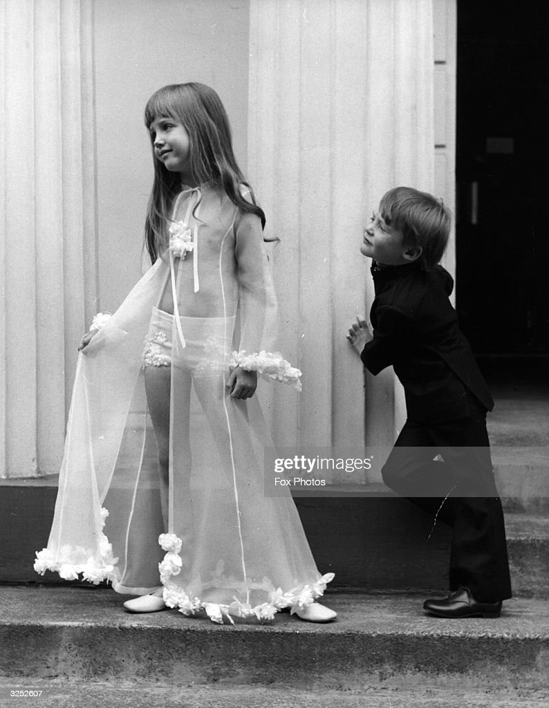 Six-year-old Yasmin models a see-through negligee in silk organza which caught the eye of Justin aged 5 who was wearing a navy suit with bell-bottomed trousers and high collar.