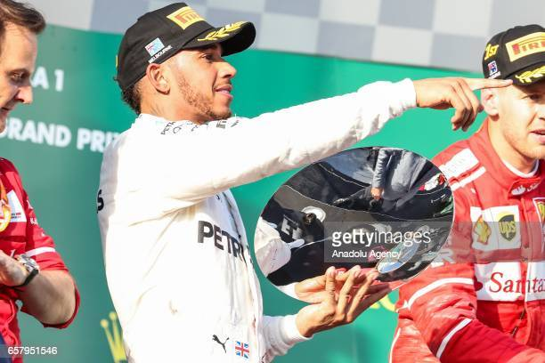 2nd place Lewis Hamilton points towards his team while he is on the podium holding his trophy during the 2017 Rolex Australian Formula 1 Grand Prix...