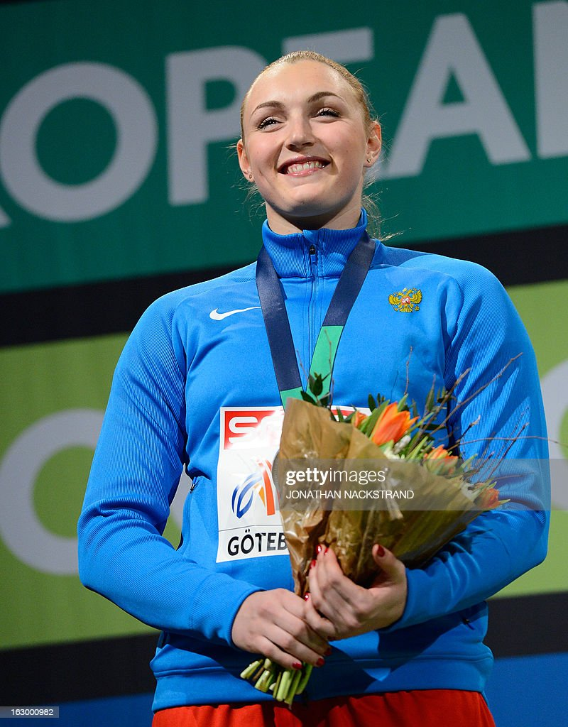 2nd place Russia's Yevgeniya Kolodko celebrates after the Women's Shot Put final event on the podium at the European Indoor athletics Championships in Gothenburg, Sweden, on March 3, 2013.