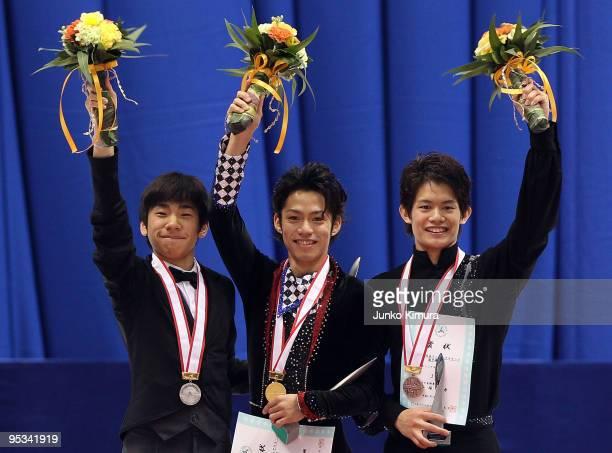 2nd place winner Nobunari Oda winner Daisuke Takahashi and 3rd place winner Takahiko Kozuka pose on the podium after competing in the Men Free...