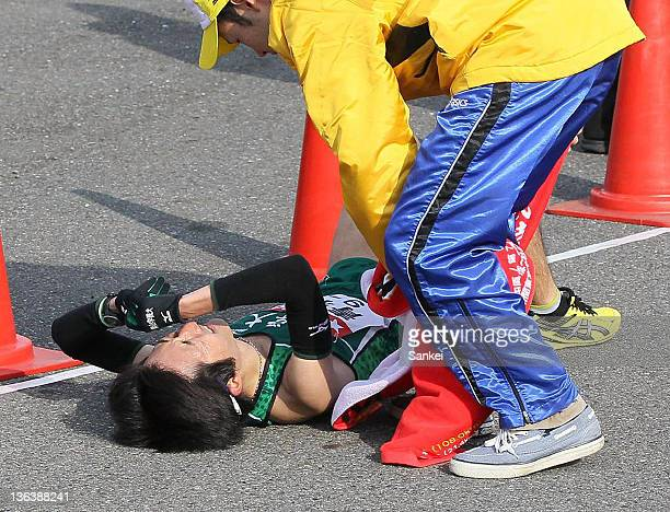 2nd runner of Aoyama Gakuin University Takehiro Deki lies on the ground after competing in day one of the 88th Hakone Ekiden on January 2 2012 in...