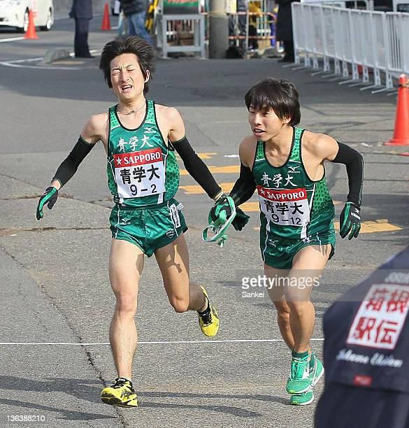 2nd runner of Aoyama Gakuin University Takehiro Deki passes the sash to Yudai Fukuda during day one of the 88th Hakone Ekiden on January 2 2012 in...