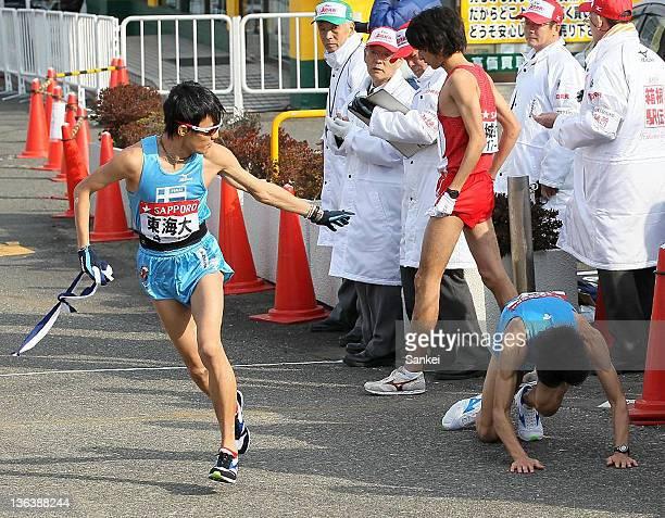 2nd runner of Tokai University Akinobu Murasawa falls on the ground after passing the sash to Kentaro Tone in day one of the 88th Hakone Ekiden on...