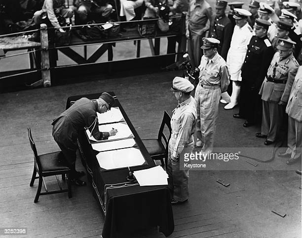 General Douglas MacArthur as Supreme Commander of the Allied Forces accepts the unconditional surrender document signed by the Japanese Yoshijiro...