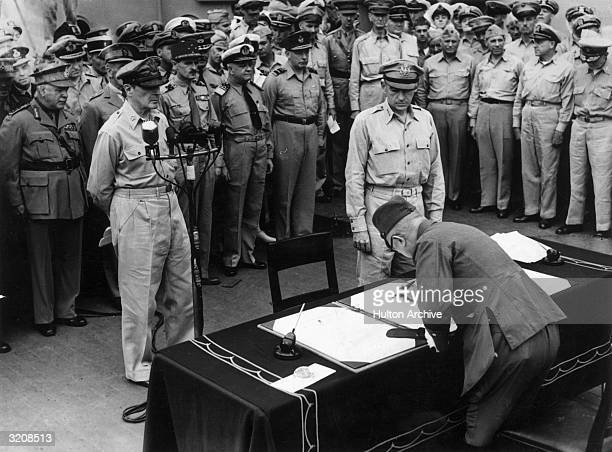 Japanese Imperial Headquarters representative General Yoshijiro Umezu signing a surrender document while General MacArthur watches aboard the USS...