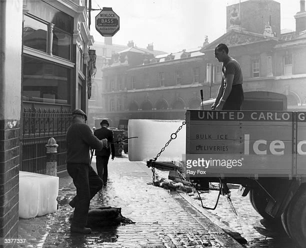 Men unloading blocks of ice at Billingsgate Fish Market in London