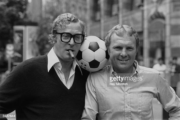 Film star Michael Caine and soccer star Bobby Moore share a football before the Charity Premiere of 'Escape to Victory' The film tells the sory of a...