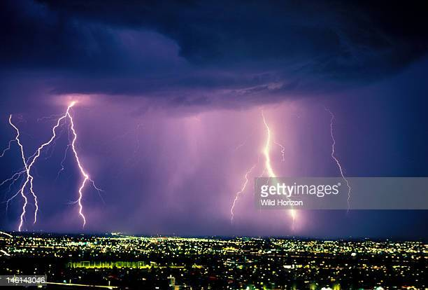 A 30second exposure of an active storm cell with multiple cloudtoground discharges over city at night Tucson Arizona USA