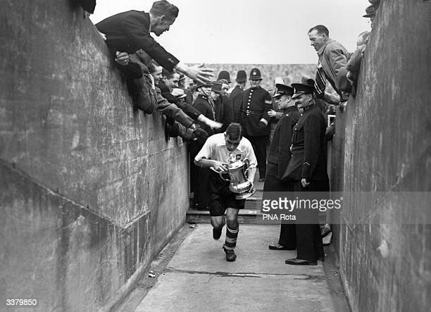 Preston North Ends' captain returns along the player's tunnel carrying the FA Cup trophy after his sides 10 victory over Huddersfield Town at Wembley