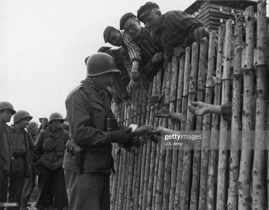 Inmates of the Dachau concentration camp lean over the edge of a wooden fence while US Corporal Larry Mutinsk distributes cigarettes to hands reaching towards him through the fence, after American troops liberated the camp, Dachau, Germany, World War II