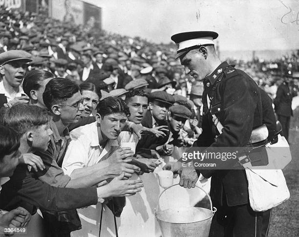 A St John's Ambulanceman gives drinks to the crowd at the football match between West Ham United and Huddersfield Town at Upton Park