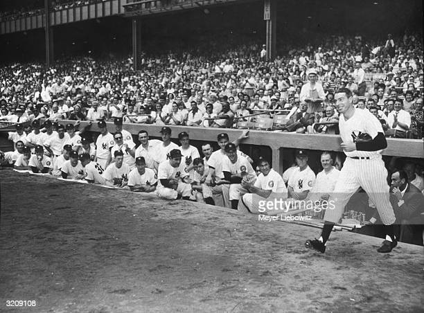 NY Yankees player Joe DiMaggio leaves the dugout at Yankee Stadium at the oldtimers game as fellow Yankees and audience members look on New York City
