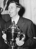 English athlete and neurologist Dr Roger Bannister with his 'Sportsman of the Year' trophy at an award ceremony at the Savoy Hotel London