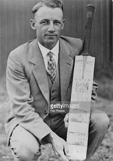 Australian batsman Don Bradman holding a personalized cricket bat