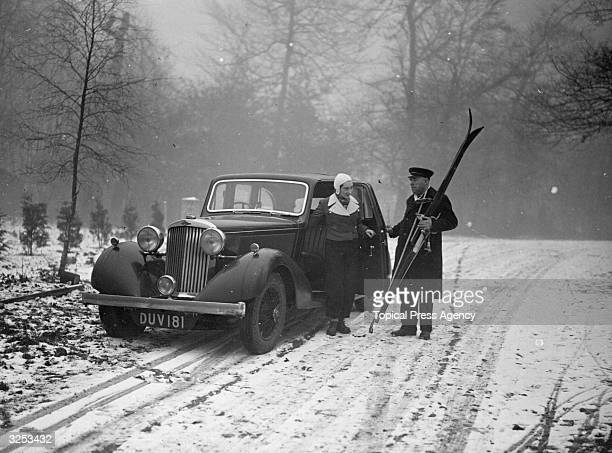 A chauffeur hands his passenger her skis at Beaconsfield Buckinghamshire for a winter sports outing