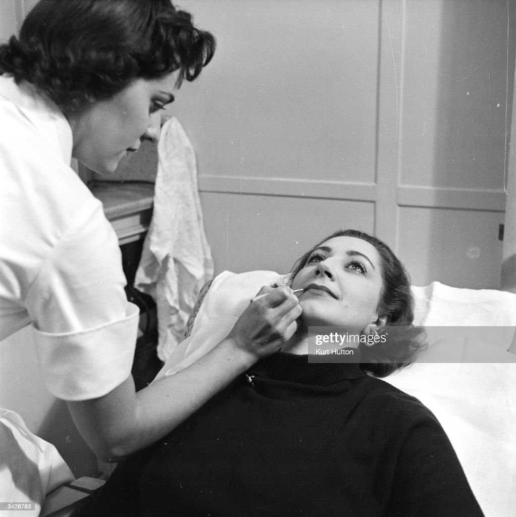 British actress Moyra Fraser has her lips painted by a beautician at one of the salons of Polish-born US businesswoman Helena Rubinstein. Original Publication: Picture Post - 6891 - The Fabulous Miss Rubinstein - pub. 1954