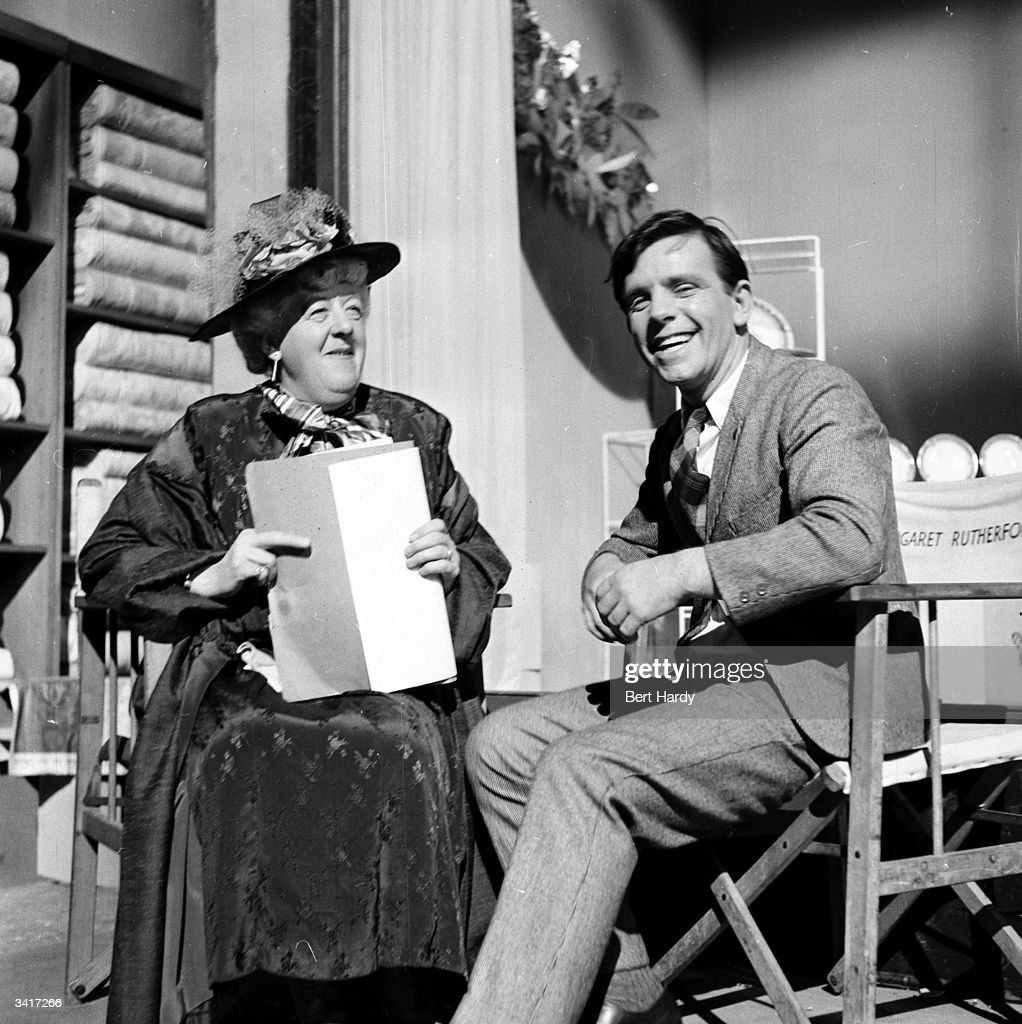 British slapstick comedian, Norman Wisdom, sharing a joke on set of his debut film, 'Trouble In Store'. Original Publication: Picture Post - 6887 - Will Norman Wisdom Be Another Charlie Chaplin - pub 1954