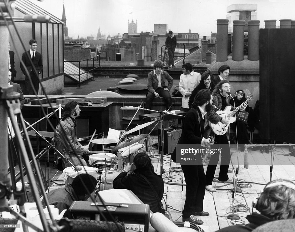 British rock group the Beatles performing their last live public concert on the rooftop of the Apple Organization building for director Michael Lindsey-Hogg's film documentary, 'Let It Be,' on Savile Row, London, England. Drummer Ringo Starr sits behind his kit. Singer/songwriters Paul McCartney and John Lennon perform at their microphones, and guitarist George Harrison (1943 - 2001) stands behind them. Lennon's wife Yoko Ono sits at right.