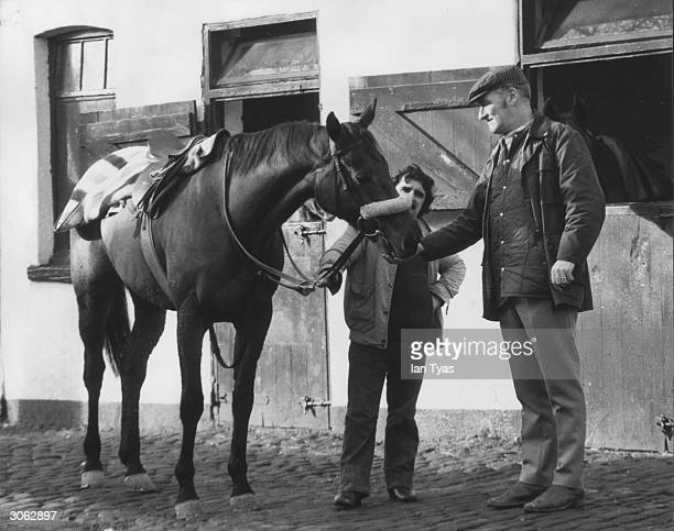 Trainer Don McCain and stable boy Billy Ellison return to the stables at Southport after exercising with Red Rum on the beach