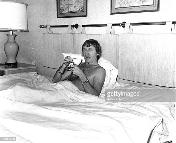 English radio disc jockey television broadcaster and charity worker Jimmy Savile enjoying a cup of tea and a cigar in bed