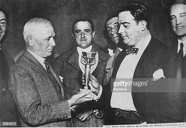 Jules Rimet president of FIFA presents the first World Cup trophy to Dr Paul Jude the president of the Uruguayan Football Association after Uruguay...