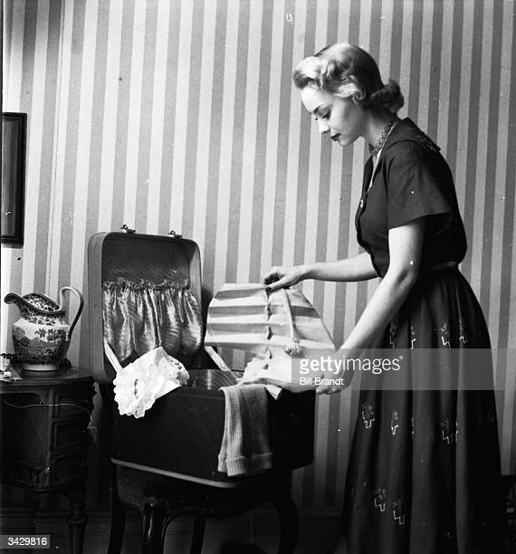 A woman unhooks the petersham headband of a mauve hat and spreads it out flat making it easy to pack into the suitcase for holiday wear Original...
